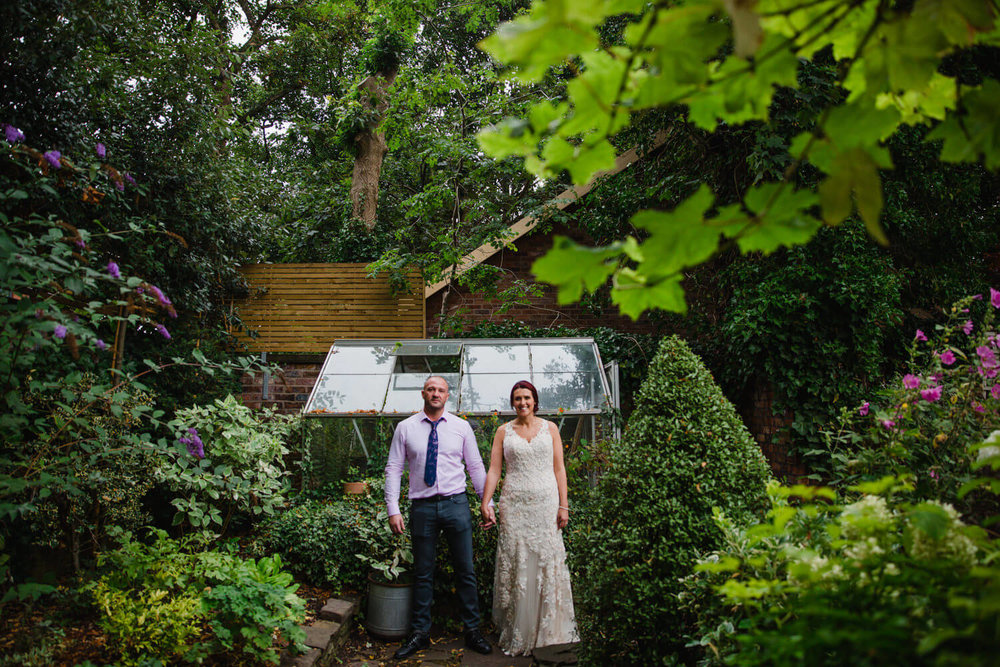 bride and groom holding hands looking straight into the camera with greenhouse in background surrounded by garden greenery