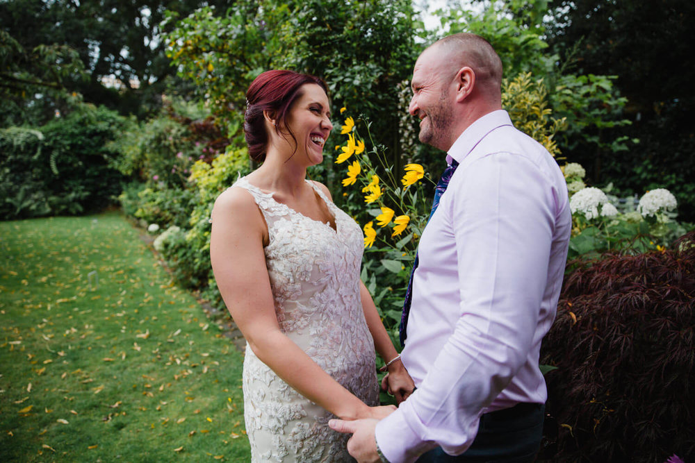 newlyweds laughing at each other while holding hands in garden