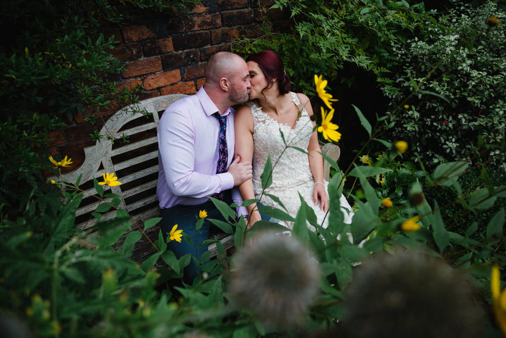 intimate moment between bride and groom sat on bench in garden on wedding day