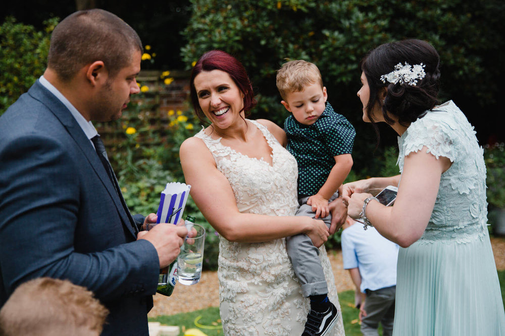 Bride holding her son while talking to wedding guest. Bridesmaid plays with pageboy