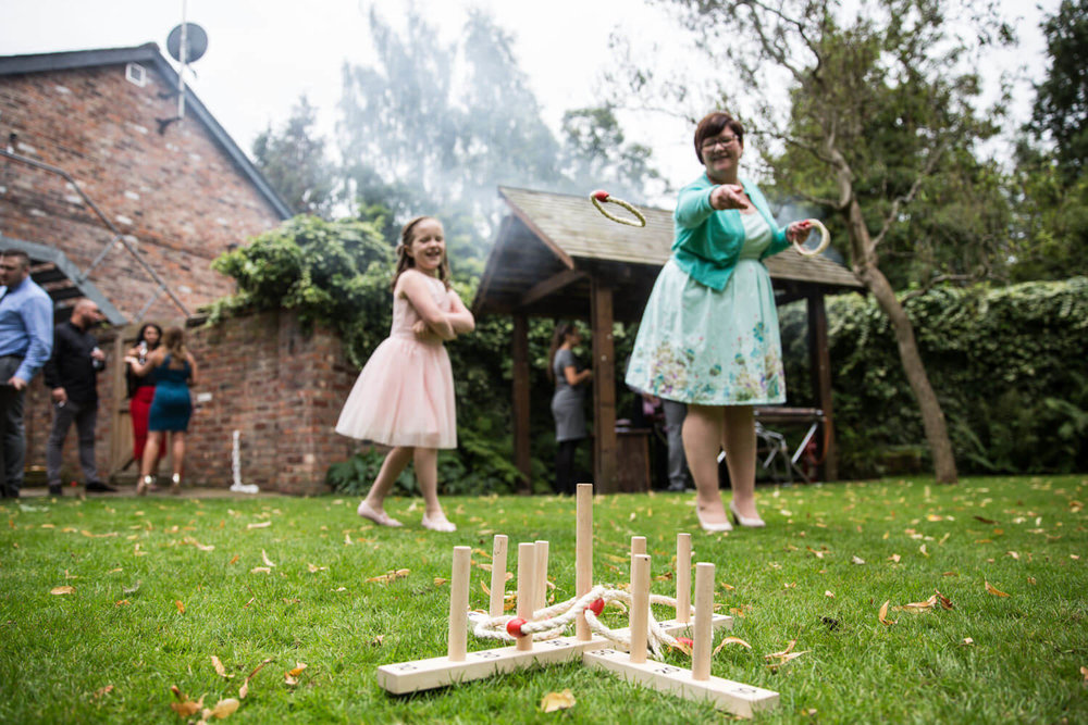 wedding guests play lawn games with hoops and pegs on grass