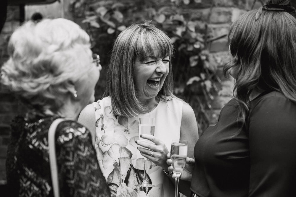 black and white photograph of wedding guest laughing with friends