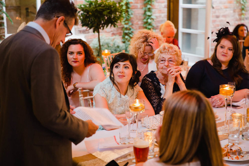 bridesmaid looks on at father giving his speech