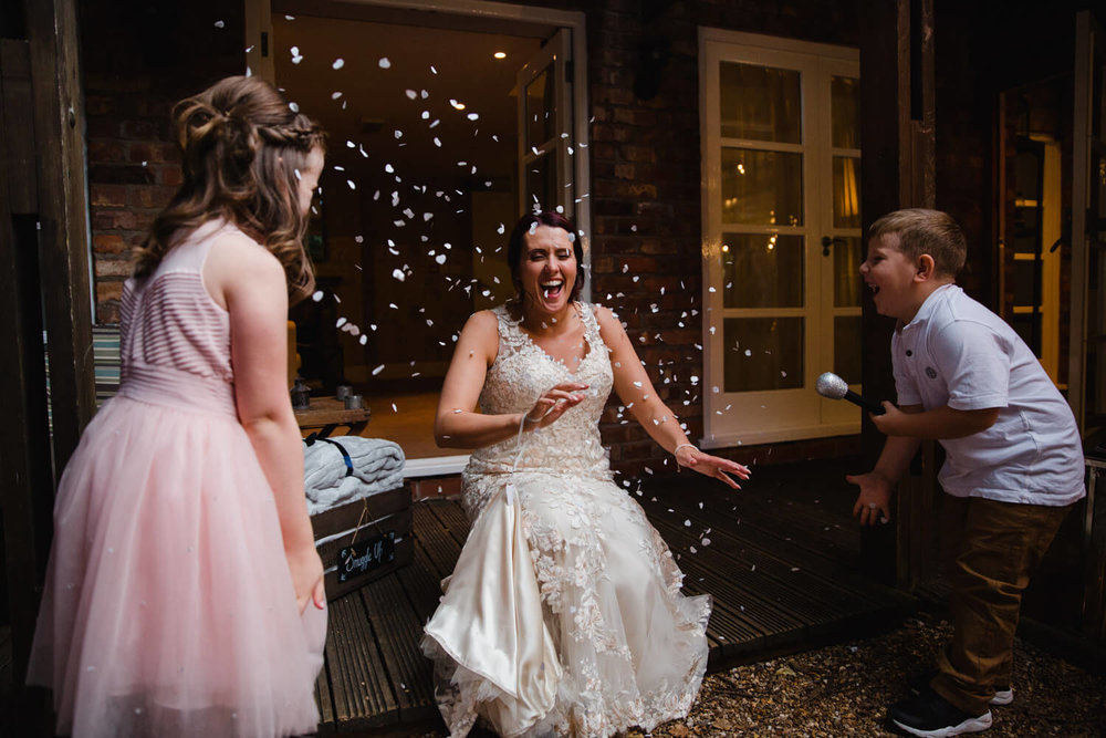 bridesmaid and page boy throwing confetti over bride after wedding reception