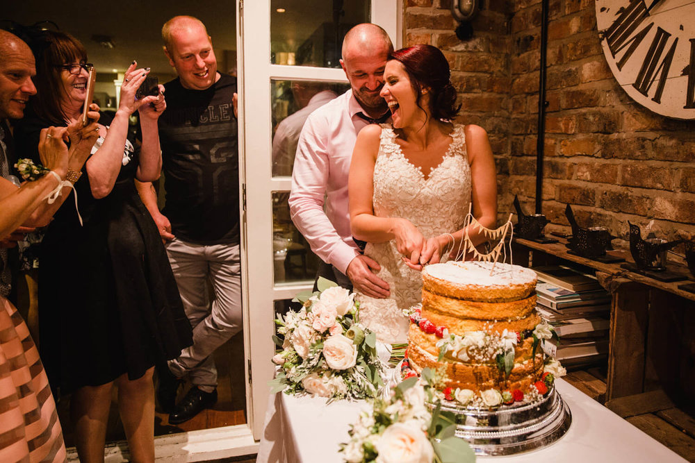 newly married couple cutting wedding cake while being photographed by friends and family