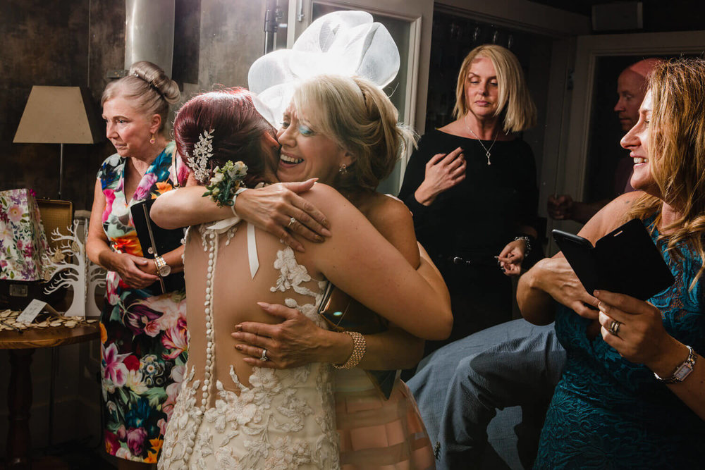 mother of bride sharing hug with daughter on dance floor