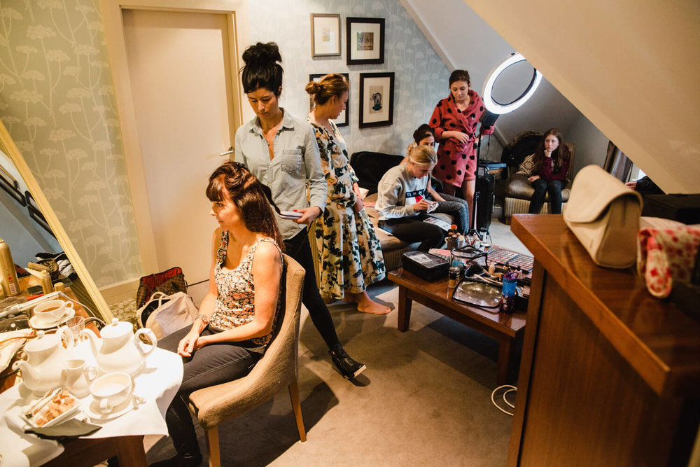 Black and white photograph of bridal party getting prepared and bridesmaids having make up done