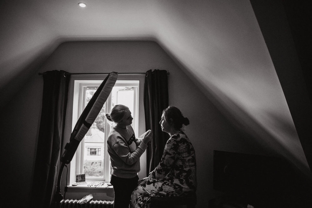 black and white photograph of bridesmaid receiving make up in the window of the bridal suite