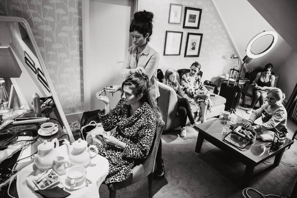 black and white photograph of bridal suite and bridesmaids getting ready in the morning