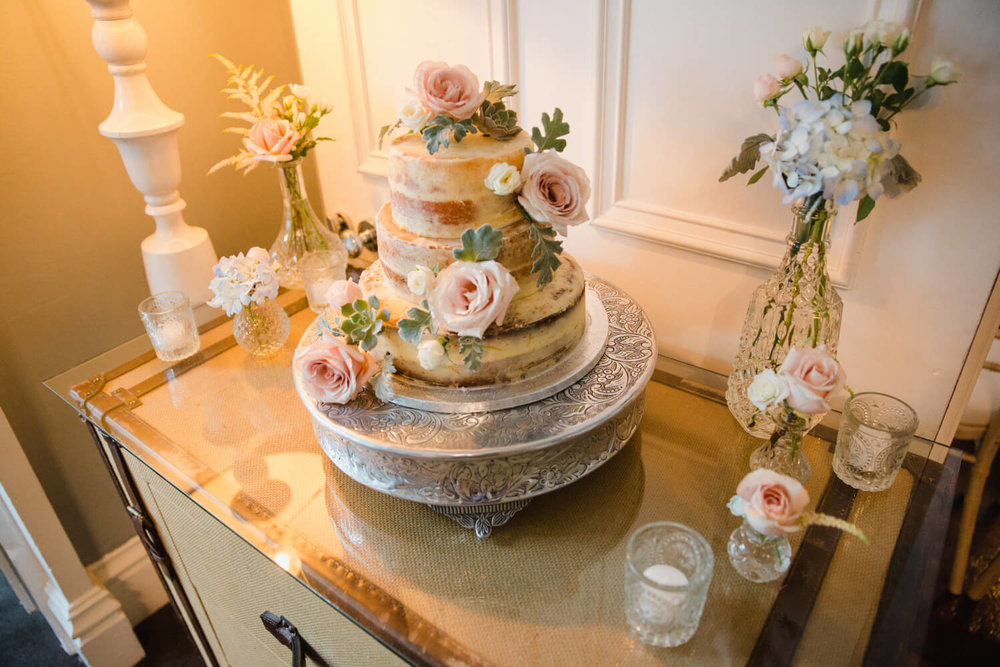 close up detail photograph of the wedding cake dressed with flowers