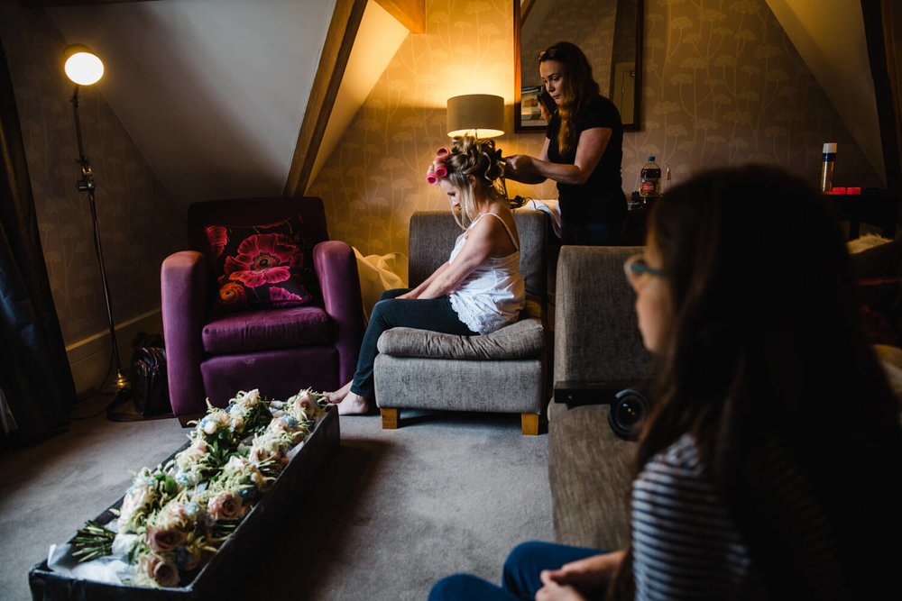 bride having her hair done by hairdresser in the light of the window with wedding bouquets on the floor in a line