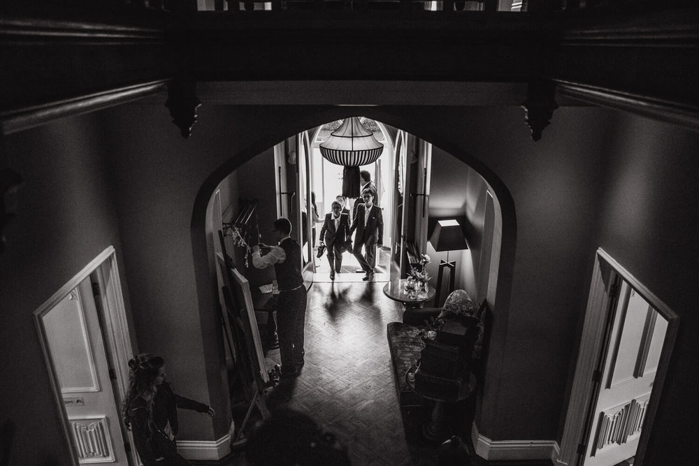 page boys entering wedding venue through front door and walking into hallway