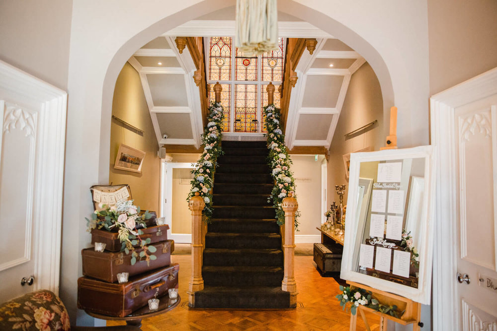 staircase dressed with flowers with suitcase for wedding cards and gifts and a mirror seating plan sat on an easel
