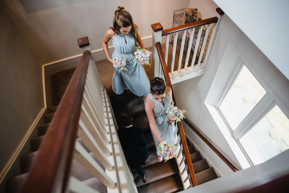 photograph from the top looking down at bridesmaids in blue dresses holding bouquets walking down staircase