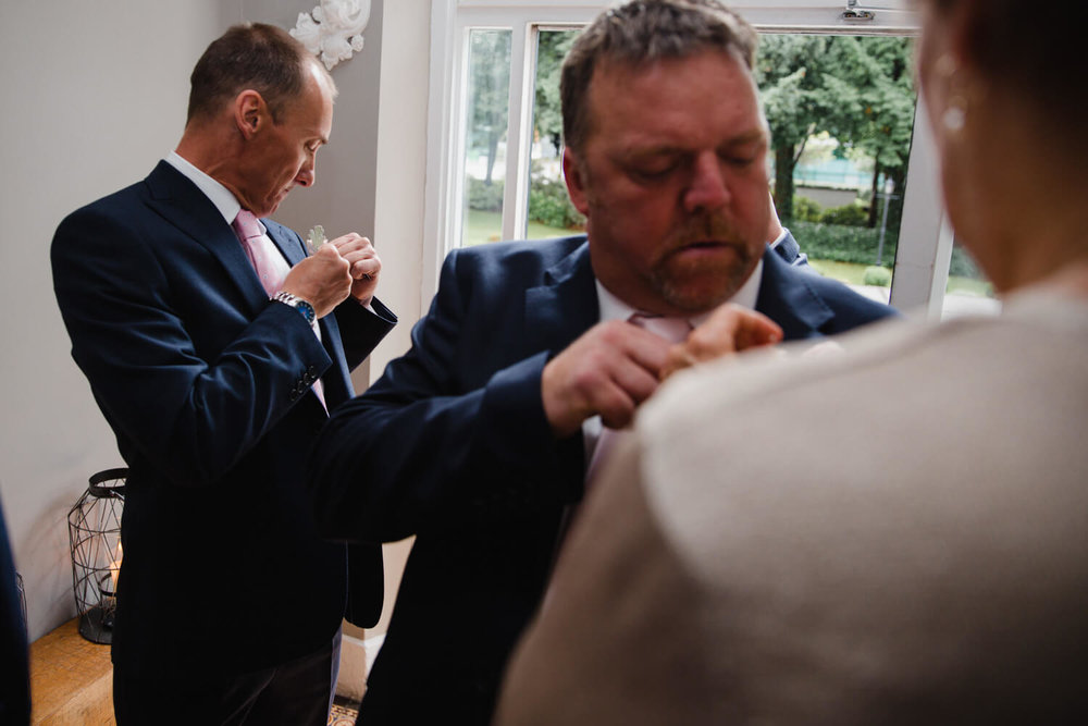 groom fixing flower pinhole fasten to his suit. Best man in foreground attaching flower to his lapel