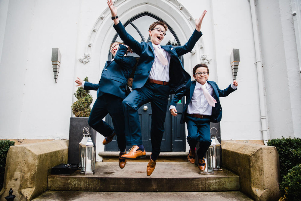 three pageboys jumping off steps in entranceway of didsbury house hotel