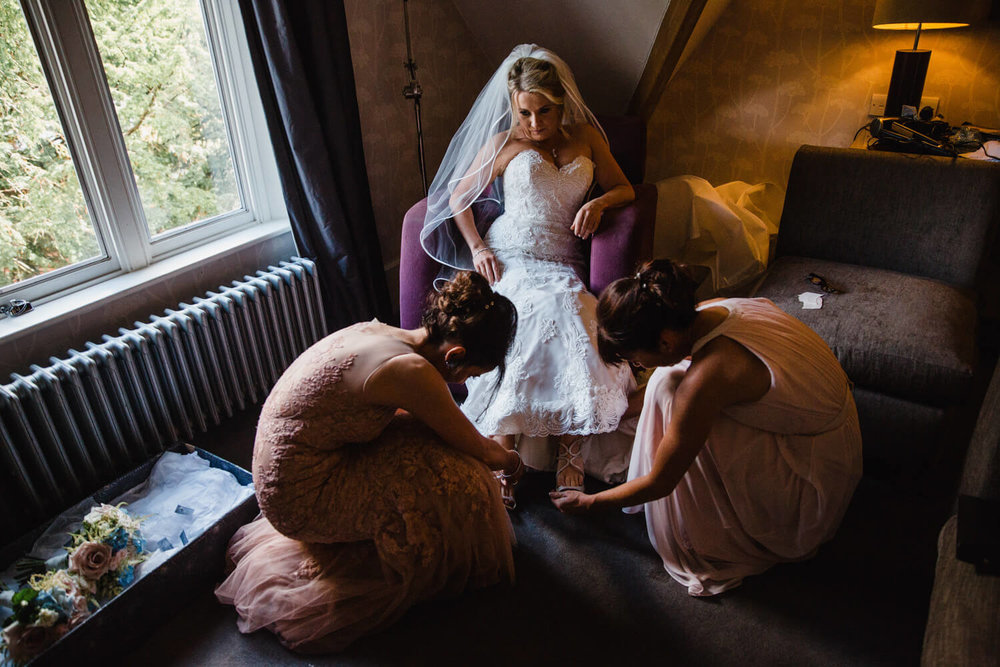 bride sits in chair while two of her bridesmaids fasten her shoes