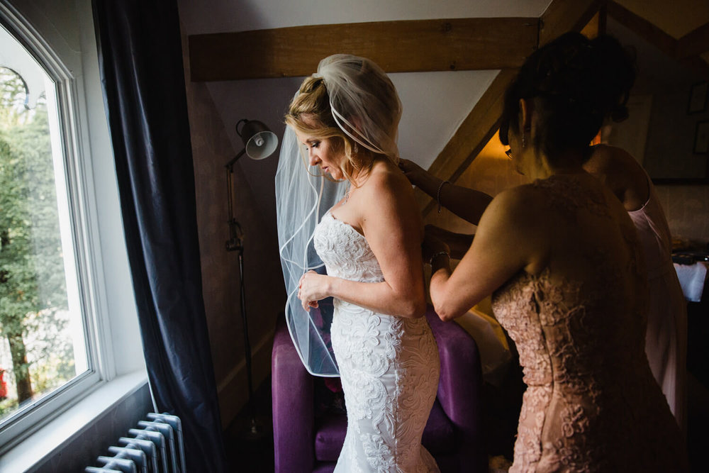 bridesmaids fasten up brides dress in the window light of bridal suite at didsbury house hotel