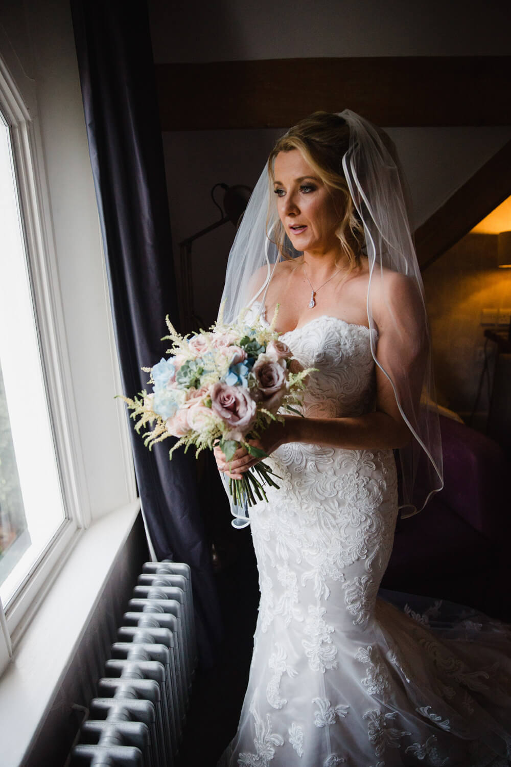 bride holding bouquet of flowers while looking out of the window