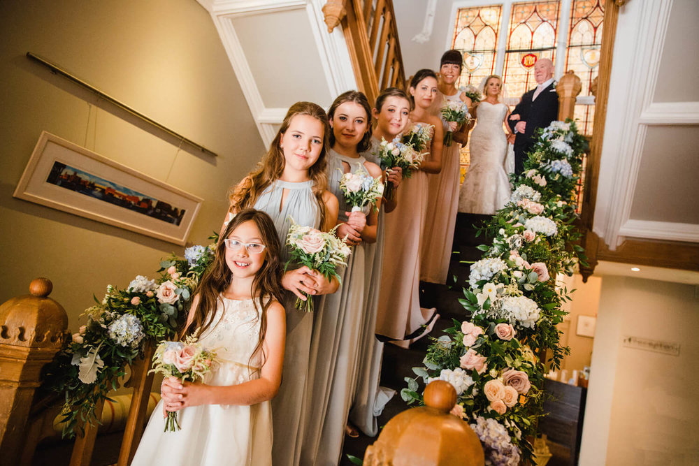 flower girl, bridesmaids, bride and father on the staircase of didsbury house hotel. The staircase dressed with flowers.