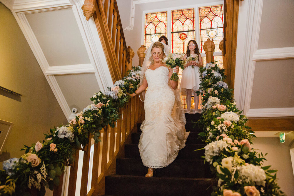 bride making her way down the staircase at didsbury house hotel