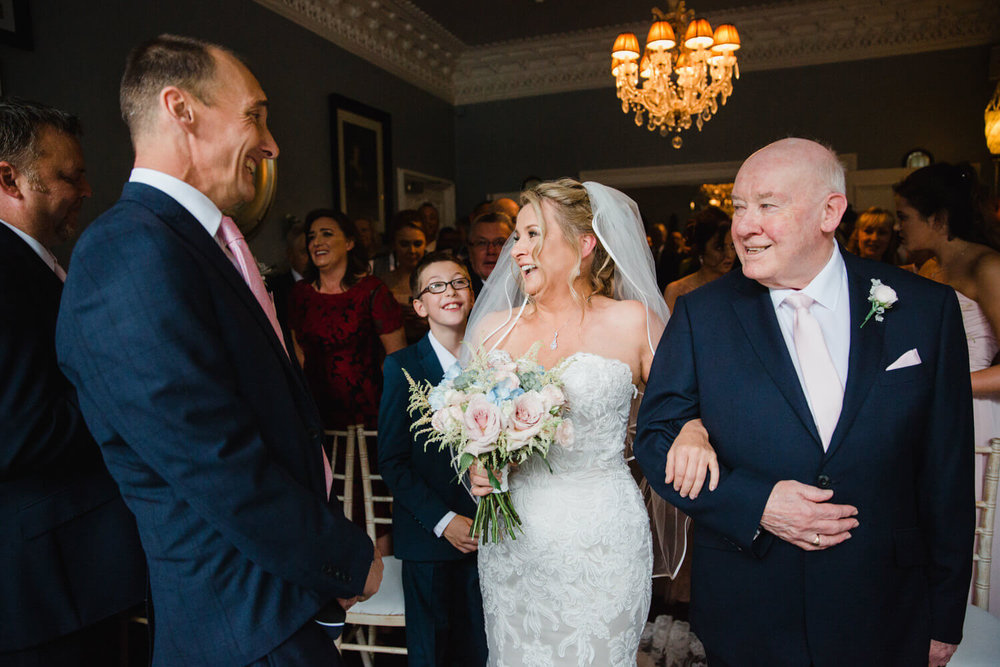 bride linking arms with dad at the top of the aisle and sharing a joke with the groom
