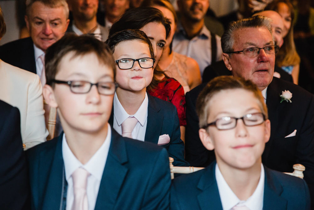 page boy wearing glasses on the knee of groomsman with a big grin on his face