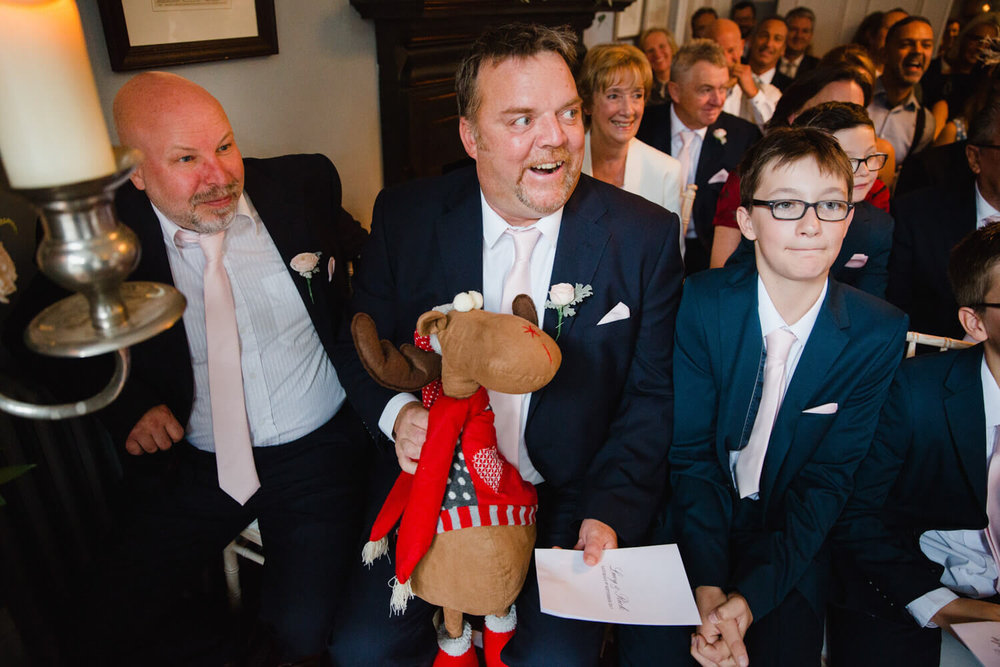 best man holding reindeer and joking around next to groomsman