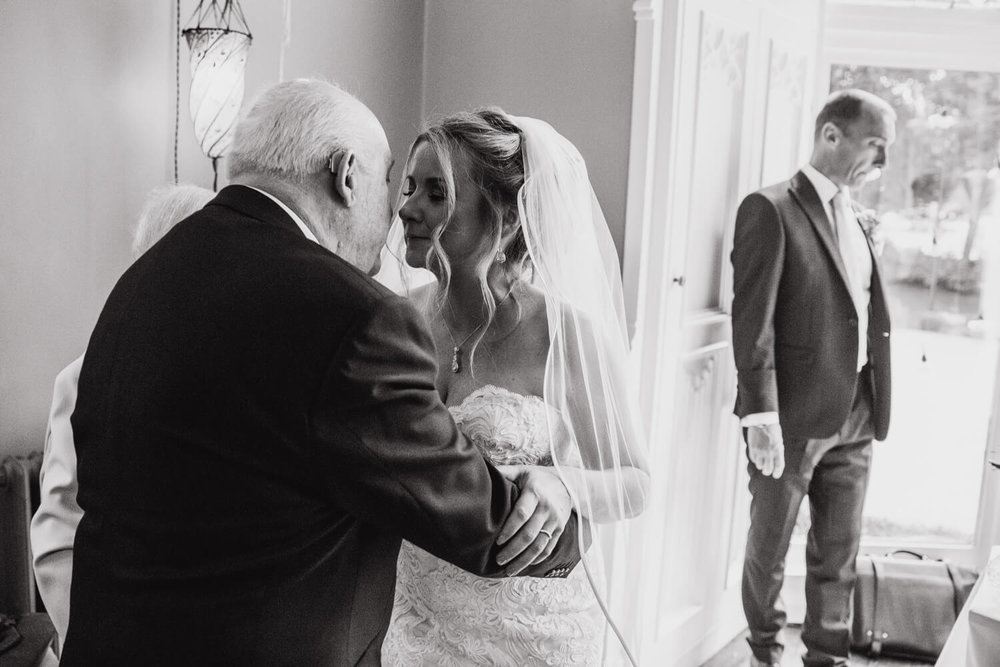 black and white photograph of bride sharing intimate moment with her father at the top of the aisle