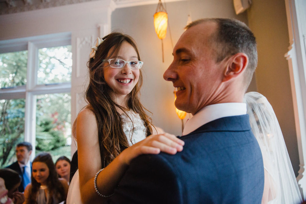 flower girl with a big smile being lifted up by groom after ceremony
