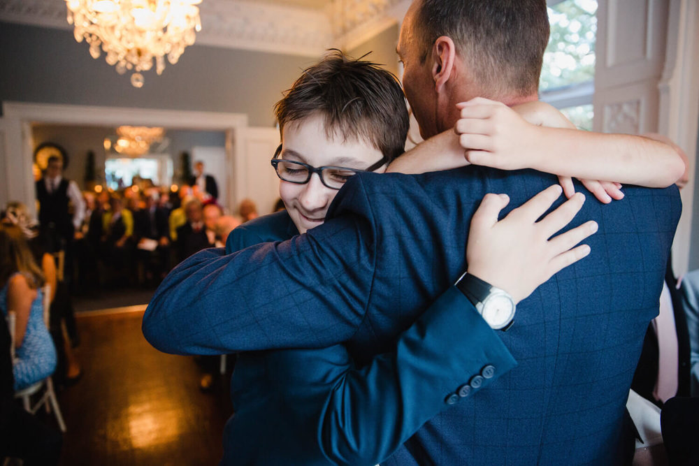 groom and his eldest son sharing an intimate hug after the wedding ceremony