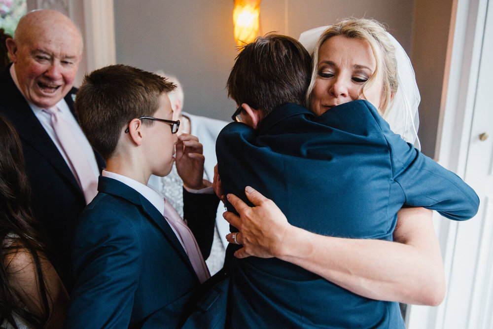 intimate moment with the bride hugging her sons