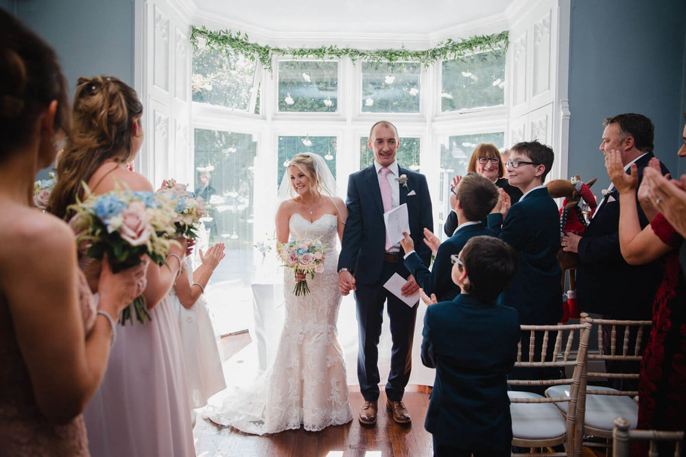 newlyweds turning to face the aisle to be congratulated by friends and family