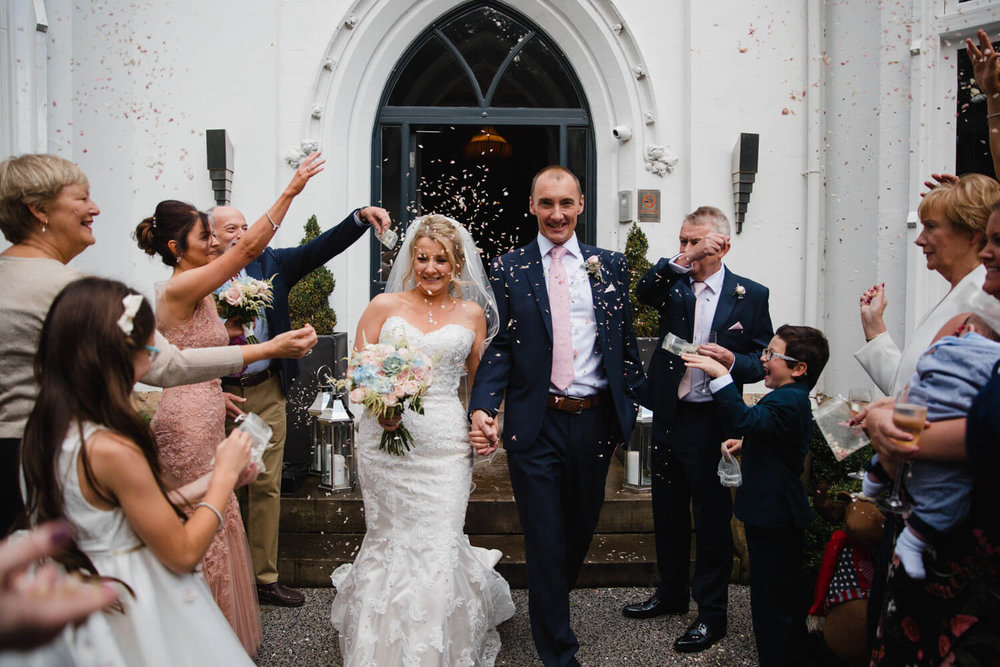Wedding party throwing confetti on bride and groom outside of didsbury house hotel