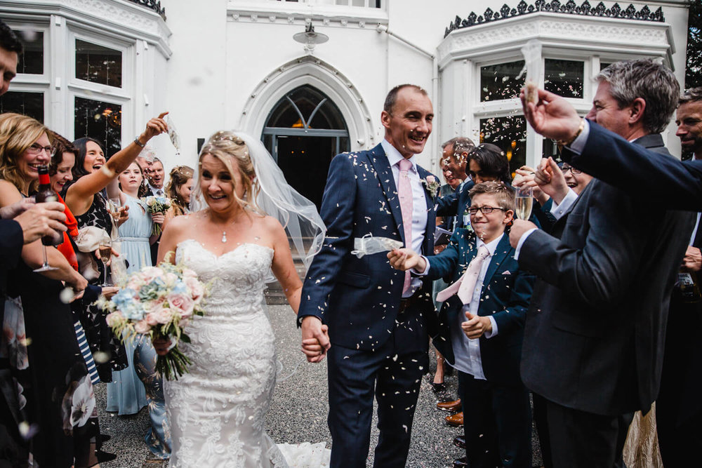 Confetti being thrown over wedded couple after ceremony