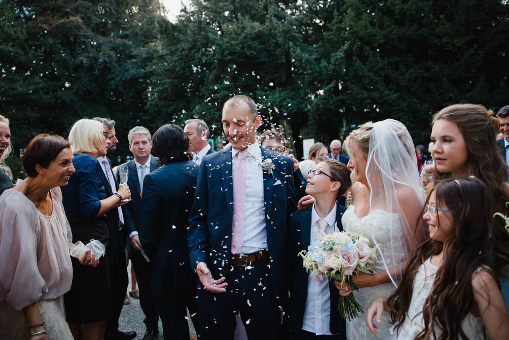 groomsmen throw confetti over groom as guests enjoy the cocktail hour
