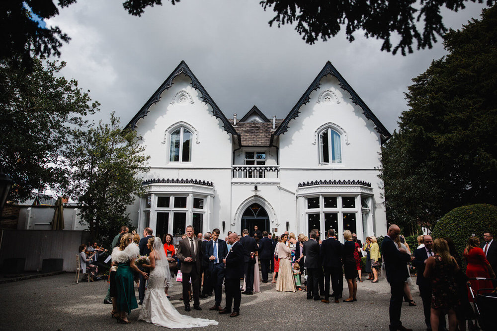 wide angle photograph with didsbury house hotel backdrop and wedding guests chatting and socialising in the foreground