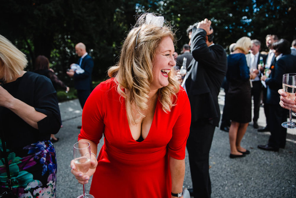 wedding guest in red dress laughing with friends