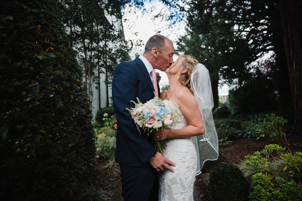 portrait of bride kissing groom in the gardens of didsbury house hotel