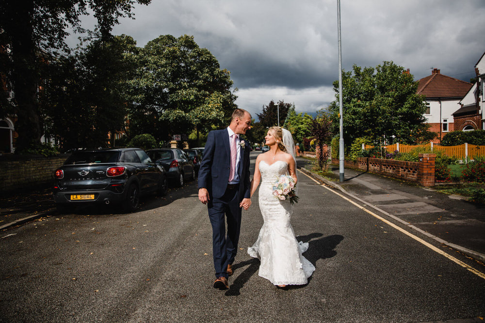 wedding couple walking down didsbury park road hand in hand together