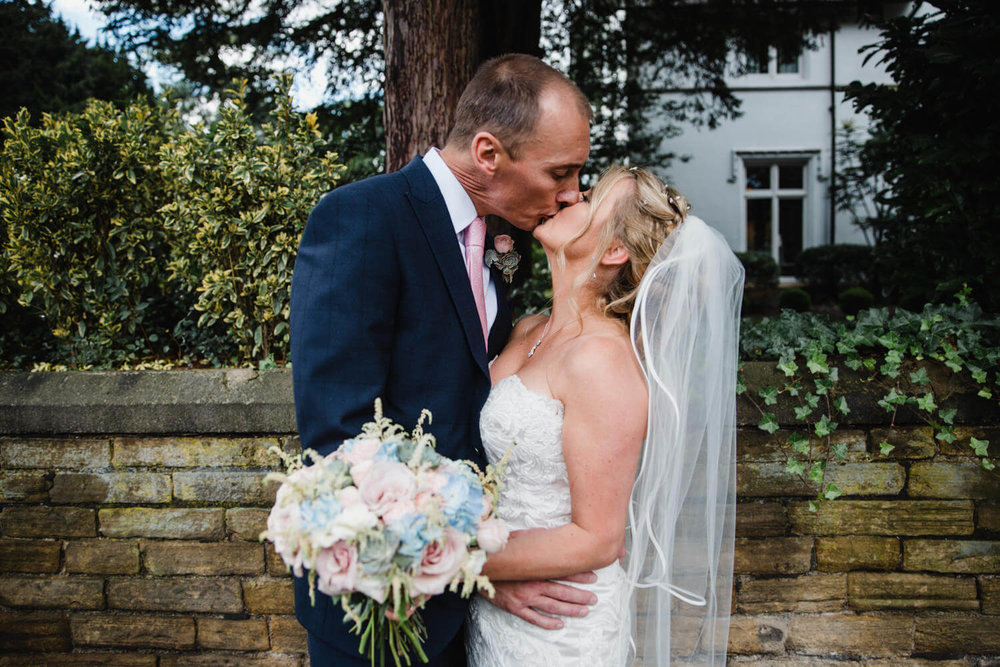 bride and groom share kiss together in front of wall at didsbury house hotel