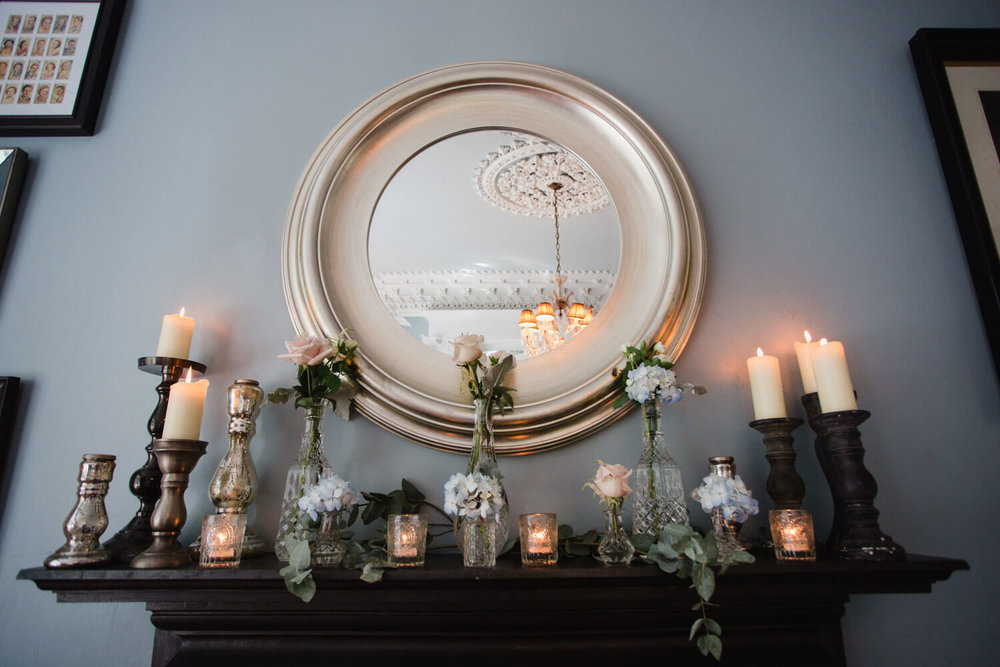 photograph of circular mirror and shelf flowers