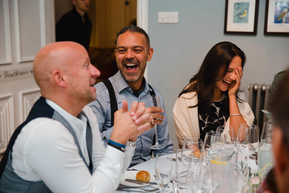 Guests laughing and joking at wedding breakfast table