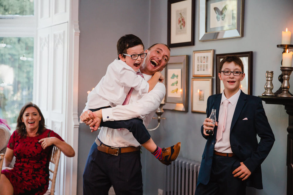 groom holding pageboy laughing at a joke told by father of bride