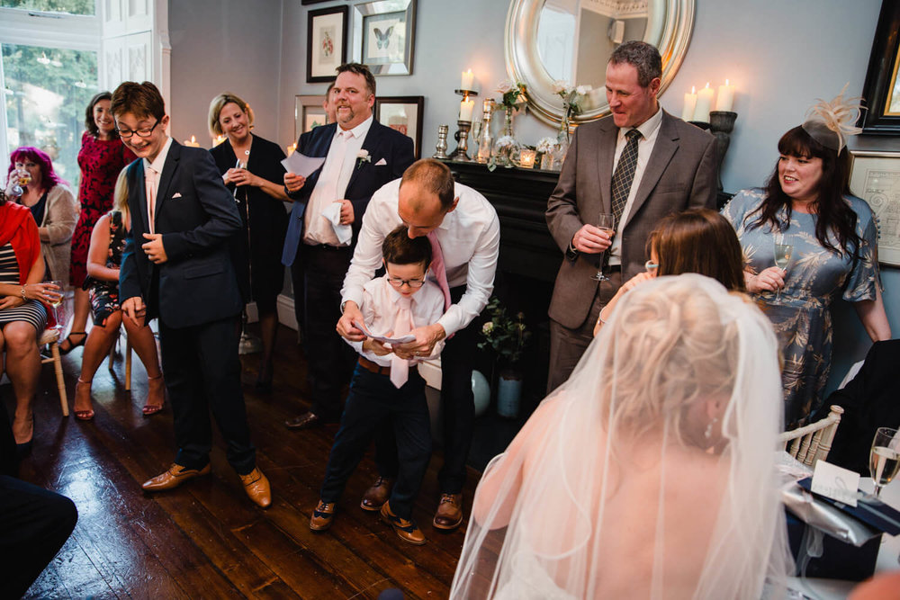 groom's son help his dad give speech to the party