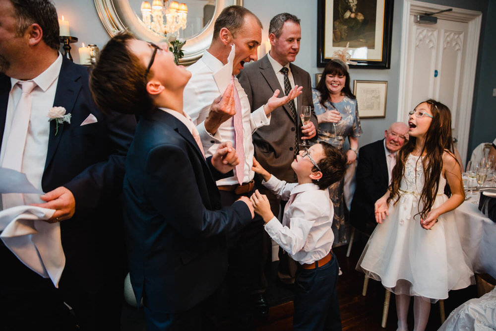 groom playing with his son during the speech with all guests laughing at them