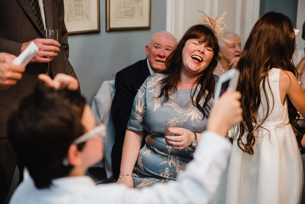 lady guest with glass in her hand laughing at the groom giving his speech