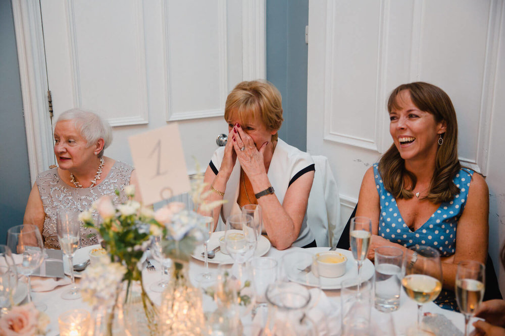 mother of groom sat at table with head in her hands laughing out loud