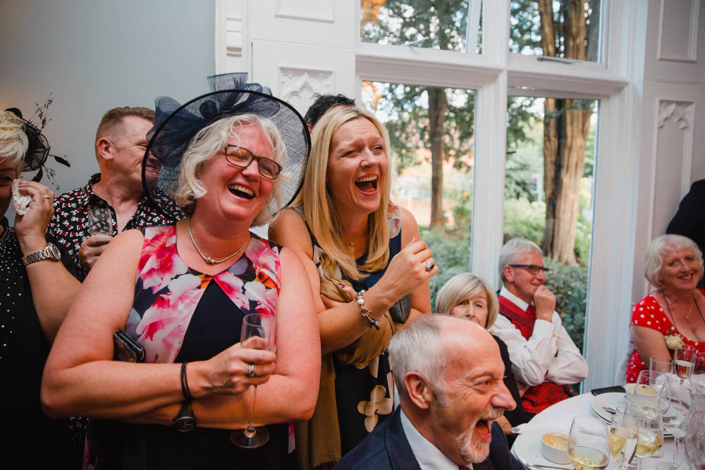 two wedding guests holding drinks and laughing together at the speeches