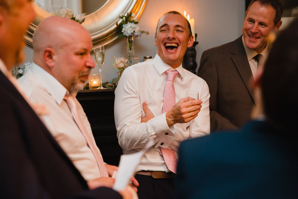 close up of groom laughing with best man during speeches